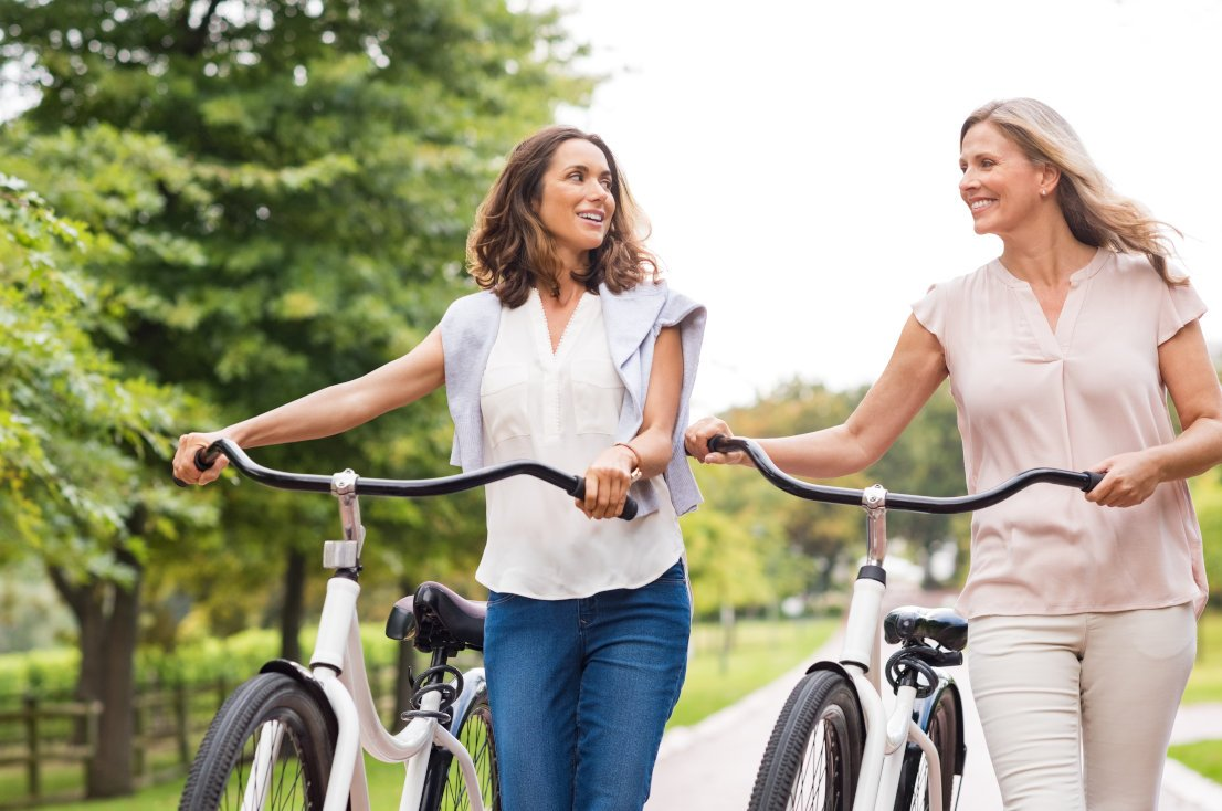 two women beside their bicycles walking